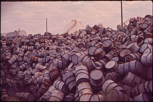 A_MOUNTAIN_OF_DAMAGED_OIL_DRUMS_NEAR_THE_EXXON_REFINERY_-_NARA_-_546000
